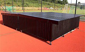 Todelt beskyttelseshus på hjul for høydehoppmatta i idrettsparken.